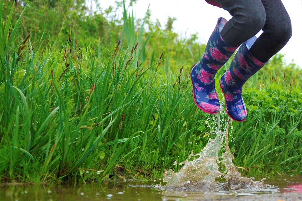 The water splashes as someone in a very colourful pair of wellington books jumps in and out of puddles